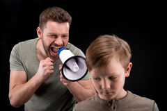 Father with megaphone screaming at scared little son Royalty Free Stock Photo