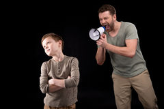 Father with megaphone screaming at son standing with crossed arms and looking away Stock Image