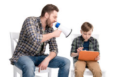 Father with megaphone screaming at son using digital tablet Royalty Free Stock Photo