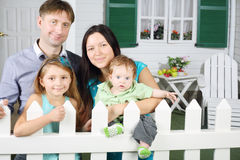 Father, mother, baby and daughter stand next to white fence Royalty Free Stock Images