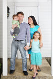 Father, mother, baby and daughter stand on porch of house. Royalty Free Stock Photos