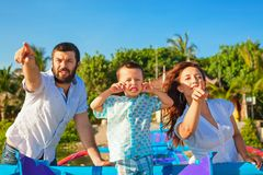 Father, mother, baby son on sea beach pointing ahead Stock Images
