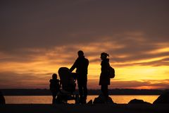 Father and mother with a baby in a stroller and children Stock Photo