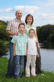 Father, mother, boy and girl is staying near pond Royalty Free Stock Photo