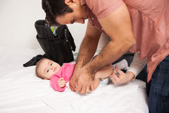 Father and mother changing baby at home Royalty Free Stock Image