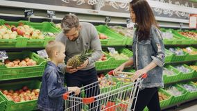 Father, mother and child are choosing pineapple in grocery store touching and smelling it showing thumbs-up. Shelves. Father, mother and cute child are choosing stock video footage
