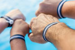 Father, mother and children hands with all inclusive bracelets. Family team by swimming pool, summer vacation, holiday resort, hotel package, fun, joy concepts royalty free stock photo