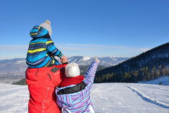 Father, mother and children are having fun and playing on snowy winter walk in nature. Royalty Free Stock Images