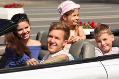 Father, mother and children ride in car. Happy father, mother and two children ride in convertible car; focus on man Stock Image