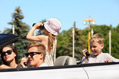 Father, mother and children ride in car Stock Images