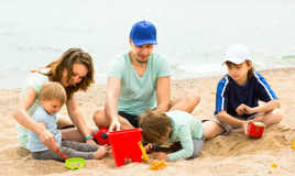 Father and mother with  children at seaside. Young father and mother with three children in vacation at seaside Stock Photo