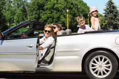 Father, mother and children sit in convertible car. Happy father, mother and two children sit in beautiful convertible car Stock Photography