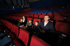 Father and mother with children watching movie Stock Photo