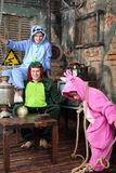 Father, mother in colorful costumes of dragons and daughter. With rope play in very old room. Focus on parents royalty free stock images