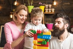 Father, mother and cute son play with constructor bricks. Educational game concept. Family on busy face spend time royalty free stock photo