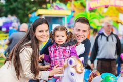Father, mother, daughter enjoying fun fair ride, amusement park Royalty Free Stock Photo