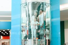 Father, mother and daughter are going down in elevator in shopping mall. royalty free stock images