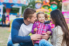 Father, mother and daughter having fun in amusement park Royalty Free Stock Photo