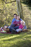 Father, mother and daughter having picnic outdoors Stock Image