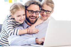 Father, mother and daughter hugging and using laptop in office Royalty Free Stock Photos