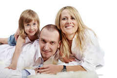 Father, mother and daughter lie on carpet Stock Images