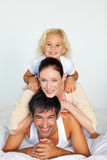 Father, mother and daughter playing in bed Royalty Free Stock Images