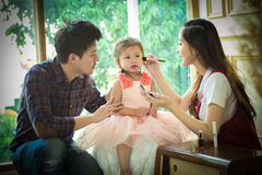 Father,mother and daughter playing with makeup. Stock Images
