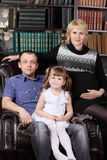Father, mother and daughter sit in armchair Royalty Free Stock Photos