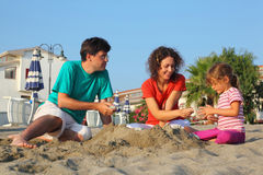 Father with mother and daughter sit on beach Stock Photography