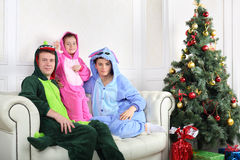 Father, mother and daughter sit on sofa near Christmas tree. Father, mother and little daughter in colorful costumes of dragons sit on sofa near Christmas tree royalty free stock photography