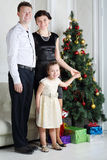 Father, mother and daughter stand near Christmas tree Stock Photography
