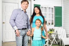 Father, mother and daughter stand next to new house Stock Images