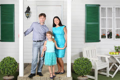 Father, mother and daughter stand on porch Royalty Free Stock Images