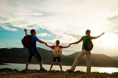 Father, mother and daughter standing on the coast of lake at the Stock Photography
