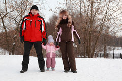 Father, mother and daughter standing at snow stock photos