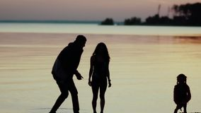 Father, mother and daughter, throw stones into the river stock footage
