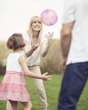 Father mother and daughter throwing ball to each other in the park Royalty Free Stock Image