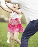 Father mother and daughter throwing ball to each other in the park Royalty Free Stock Photography