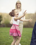 Father mother and daughter throwing ball to each other in the park Royalty Free Stock Photos