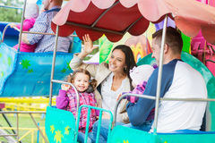 Father, mother, daughters enjoying fun fair ride, amusement park. Cute little girls with their mother and father enjoying ride at fun fair, young family Royalty Free Stock Photography