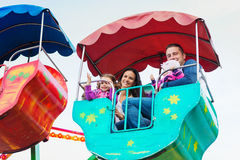 Father, mother, daughters enjoying fun fair ride, amusement park. Cute little girls with their mother and father enjoying ride at fun fair, young family Stock Photography