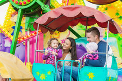 Father, mother, daughters enjoying fun fair ride, amusement park. Cute little girls with their mother and father enjoying ride at fun fair, young family Royalty Free Stock Images