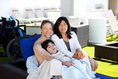 Father and mother with disabled son on blue lounger off side of. Multiracial couple with young disabled son on blue poolside lounger, drying off after swimming Stock Photos