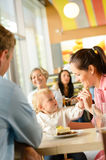 Father and mother feeding child cake cafe Royalty Free Stock Images