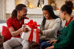 Father and mother giving Christmas gift to daughter. Father and mother giving Christmas gift to surprised daughter royalty free stock image