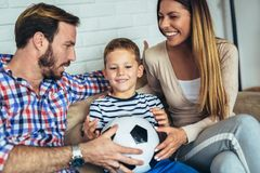 Father and mother giving a football ball to their son. At home stock photos