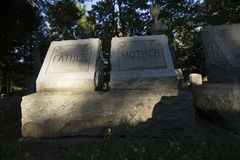 Father and Mother Grave Markers at an Old Cemetery. Father and mother grave markers and headstones, monuments and trees stand in the late afternoon light in an Royalty Free Stock Photo