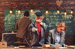 Father and mother help son doing homework in school, education stock image