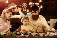 Father, mother and her child enjoy painting Easter eggs. royalty free stock photo