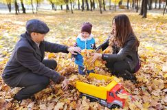 Father, mother and his little son rest in autumn garden. Cute boy playing with the toy car in the autumn park. Stock Photos